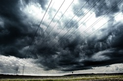 Electrical wires in country under stormy clouds