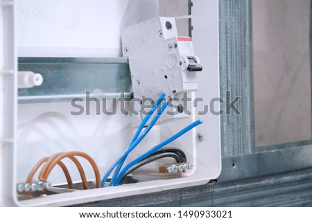 Electrical wiring in the house. A guard with machine guns and wired cables. Safe cabling in the apartment #1490933021