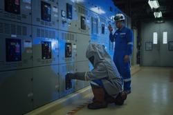 Electrical worker wearing arc flash suit protection is used to draw out a large circuit breaker.