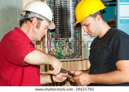 Electrician and apprentice repairing a circuit breaker from an industrial panel.