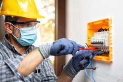 Electrician at work on an electrical panel protected by helmet, safety goggles and gloves; wear the surgical mask to prevent the spread of Coronavirus. Construction industry. Covid 19 Prevention.