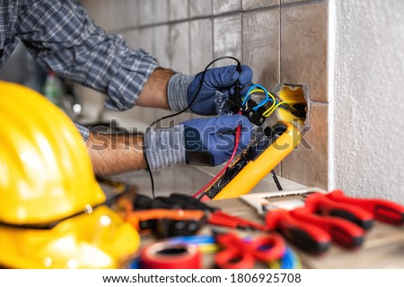 Electrician at work with the tester measures the voltage in the sockets of a residential electrical system. Construction industry.  Сток-фото ©