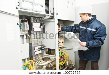 Electrician builder at work inspecting cabling connection of high voltage power electric line in industrial distribution fuseboard