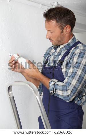 Electrician changing lamp bulb