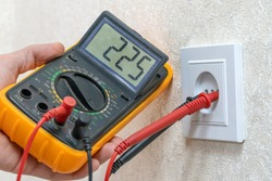 Electrician checks the voltage of the outlet using a digital multimeter, close-up