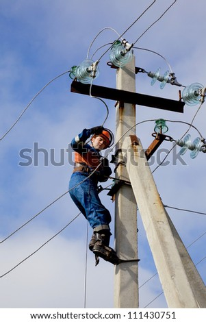 Electrician connects wires on a pole against the blue sky
