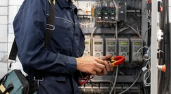 Electrician engineer checks electrical circuit in control panel for high current and voltage, starting and commissioning relays for industrial production.