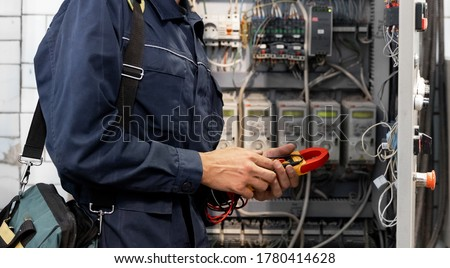 Electrician engineer checks electrical circuit in control panel for high current and voltage, starting and commissioning relays for industrial production. Stock photo ©