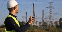 Electrician Engineer Man Using Digital Tablet Working in Fossil Energy Power Plant Utility Building