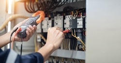 Electrician engineer work tester measuring voltage and current of power electric line in electrical cabinet control , concept check the operation of the electrical system .
