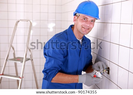 Electrician fitting a light switch in a large white tiled room