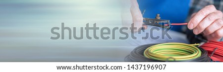 Electrician hands stripping a wire. panoramic banner #1437196907