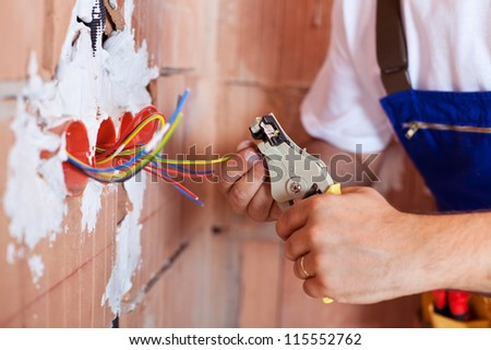 Electrician hands with pliers and a bunch of wires - stock photo