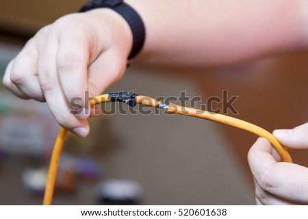 Electrician holding Portable appliance (PAT) test failure due to damaged cable. Badly repaired. Selective focus on the cable