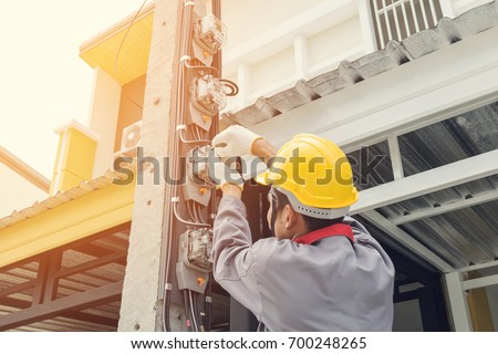 Electrician in a gray uniform wears gloves and a helmet installing a power meter on an electricity pole. stock photo