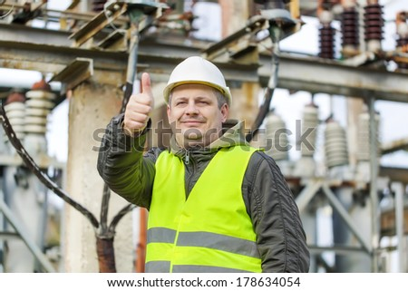 Electrician in electrical substation near to high-voltage cable