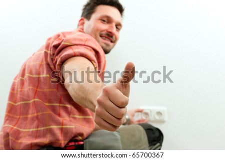 Electrician installing a power socket giving the thumbs-up sign - focus on thumb