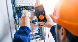 Electrician installing electric cable wires and fuse switch box. Multimeter in hands of electricians detail.
