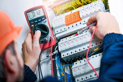 Electrician installing electric cable wires and fuse switch box. Multimeter in hands of electricians.