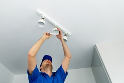 electrician installing led light bulbs in ceiling lamp