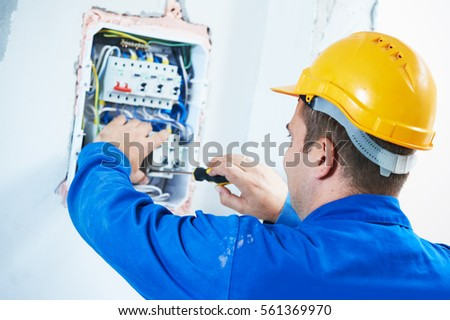 electrician installing switching electric actuator in fuse box