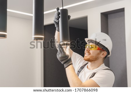 Electrician installs lamp lighting and spot loft style on ceiling. Stock photo ©