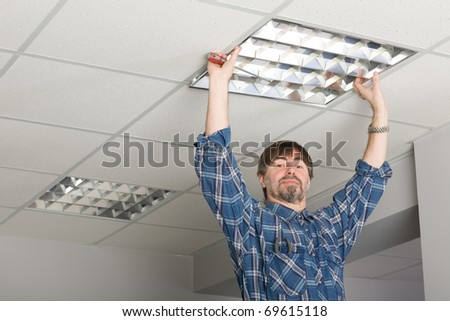 Electrician installs lighting to the ceiling in the office.
