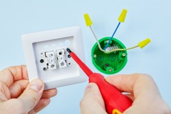 Electrician is installing new double light switch with help of screwdriver.