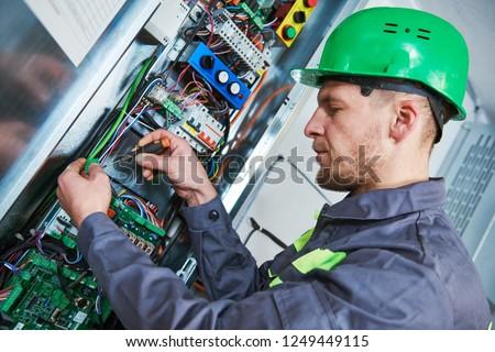 Electrician make maintenance in engine room of elevator