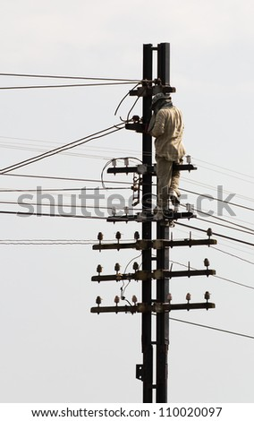 Electrician Man on electric poles. Repairs a Wire of the power line