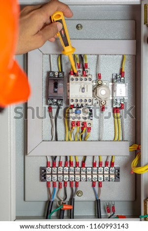 electrician man testing electrical terminal box, control panel with  magnetic contactor and overload relay,