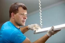 Electrician man worker installing ceiling fluorescent lamp