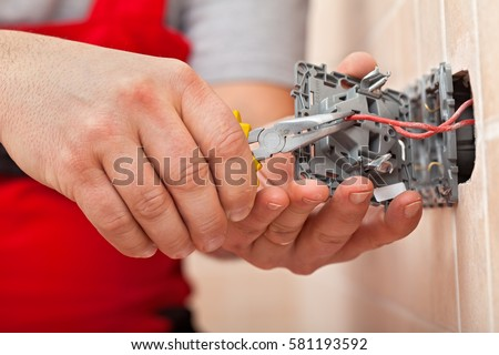Electrician mounting the wires into electrical wall fixture or socket - closeup on hands and pliers