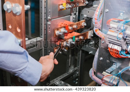 Electrician near the low-voltage cabinet. Uninterrupted power supply. Electricity.