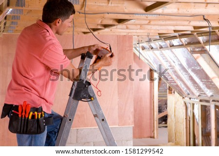 Electrician on stepladder working in new house on construction site