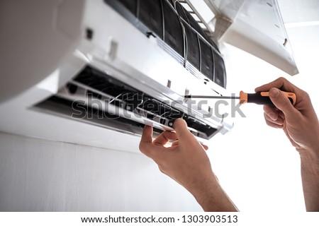 Electrician repairing air conditioner indoors ストックフォト ©