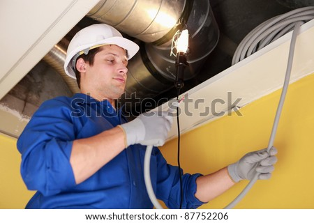 Electrician repairing ceiling wiring - stock photo