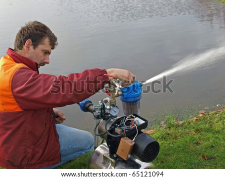 Electrician repairing the water pump near pond