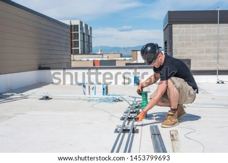 Electrician running wire through conduit on a building roof top. Stock photo ©