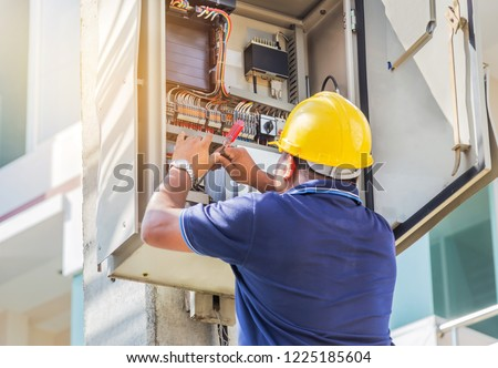 Electrician screwing equipment repairing in fuse circuit breaker box