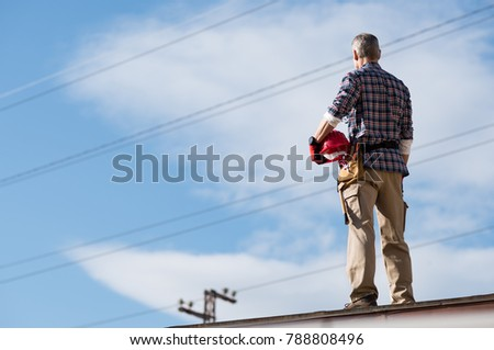 Electrician standing on top roof and looking away while thinking. Rear view of construction worker holding safety helmet looking at electric cables. Electrical engineer look at power line.