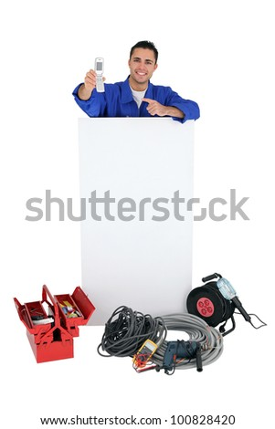 Electrician stood by poster pointing at mobile telephone