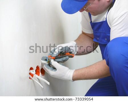 Electrician stripping electrical wires for wall socket