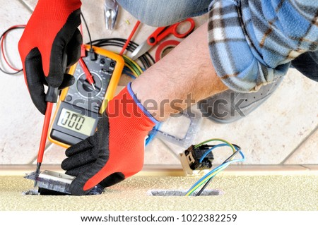 Electrician technician at work fixes the support screw in a residential electrical installation