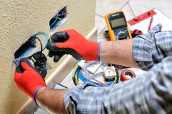 Electrician technician at work sticks the cable between the clamps of a socket in a residential electrical installation
