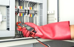Electrician technician using digital Camp amp meter to check electric current in a factory  electrical installation with  hands protected by electric hand gloves