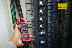 Electrician to check electric current    in cable by ampere clamp meter