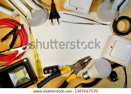 Electrician tool, frame of appliances for repair on white background. A set of tools for high-quality industrial repair of electrical wiring, lamps, floodlights, screwdriver, tape.  #1387667570