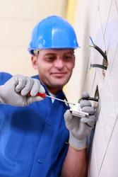 Electrician wiring a wall socket