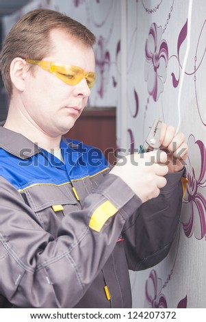 Electrician with glasses using pliers